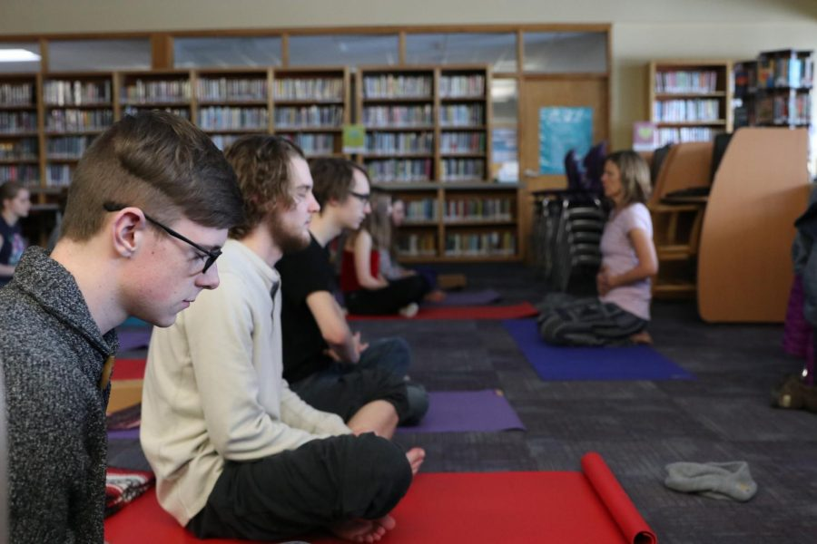 Kenyon Jones, Caden Johansen and River Nichols center themselves in the first Wednesday yoga and mindfulness class, in the library.