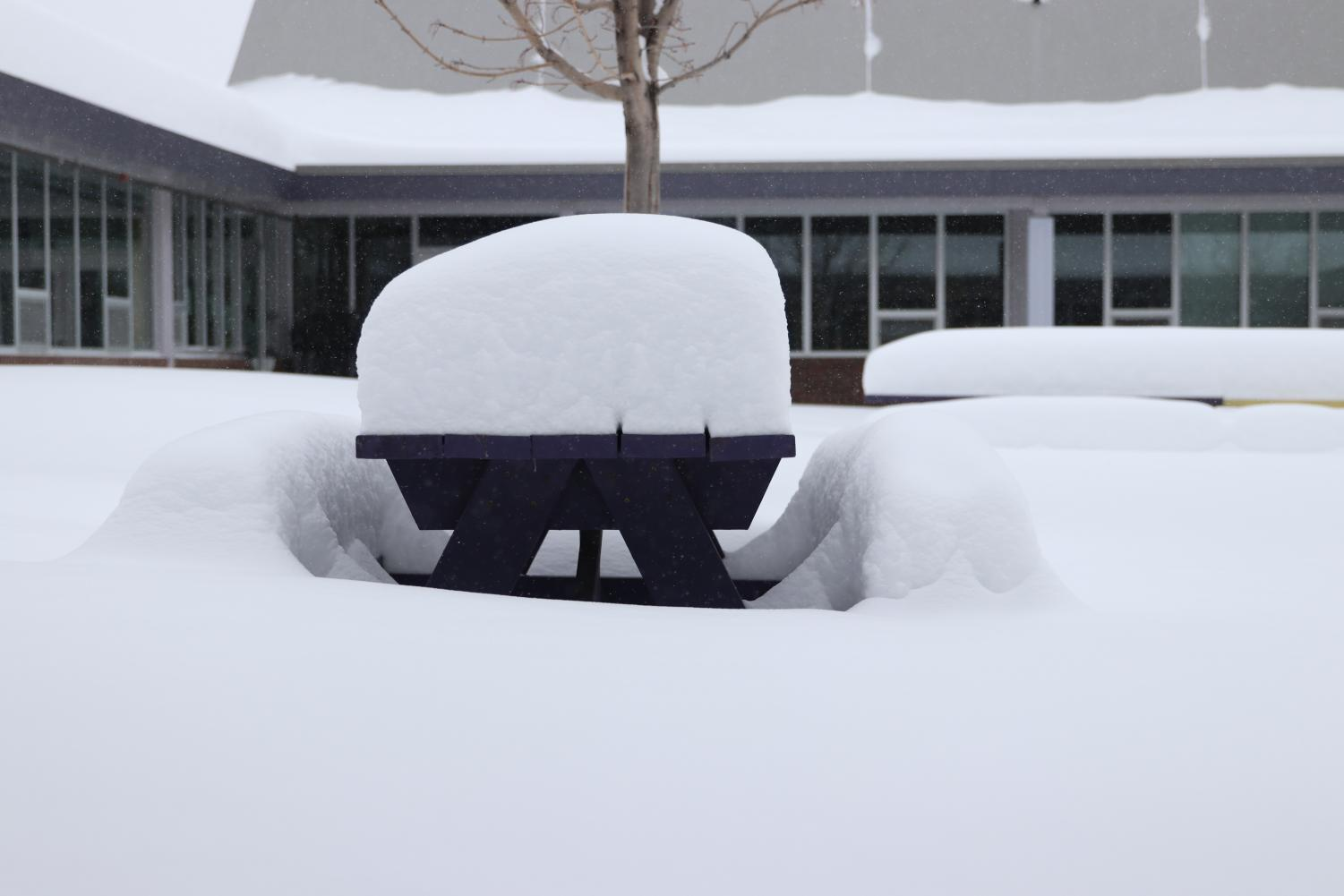 A picnic table in the courtyard is gradually disappearing in a pile of snow, Monday.