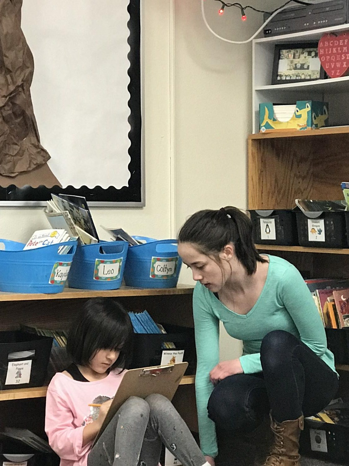 Brianna Pittman helps a first grader in Taylor Neibauer's class during her career internship seventh period.