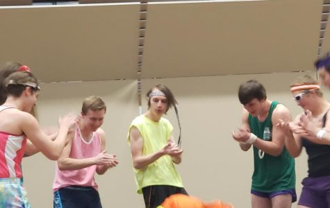 Jamison Geyer does the worm during the Mr. PHS opening number while his competitors cheer him on.