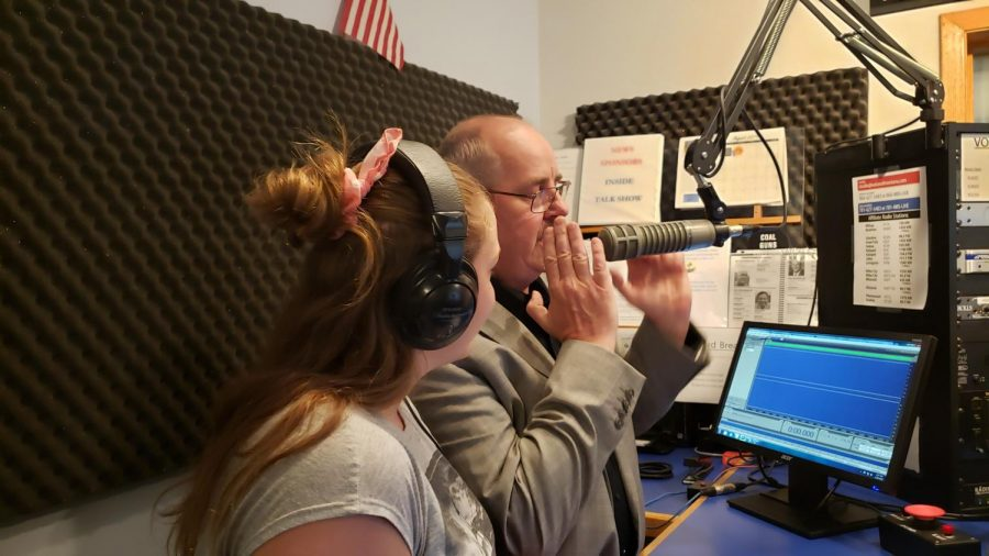 Voices+of+Montana+radio+host+Tom+Schultz+demonstrates+to+student+Desiree+Swanson+how+to+use+the+microphone+for+live+radio+broadcast.