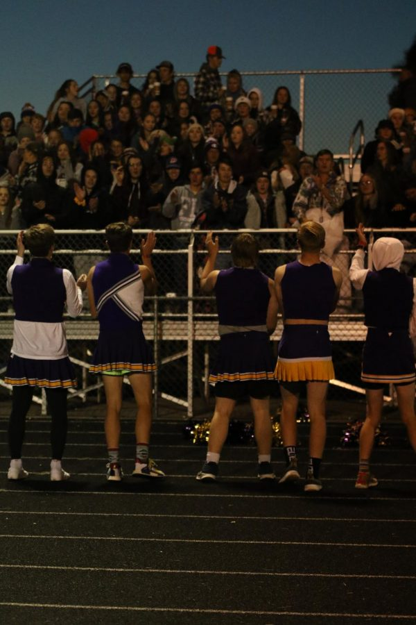 Cheerleaders encouraging school spirit with the student section during the Powder Puff game by doing the funky chicken.