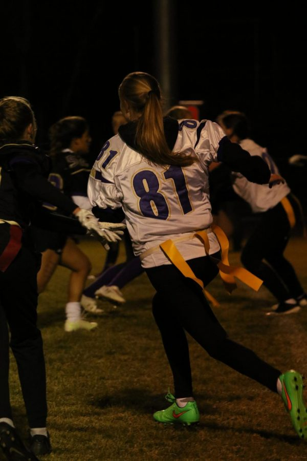 Emily Leckner runs to protect her team and the football from the Senior team during a play of Powder Puff football.