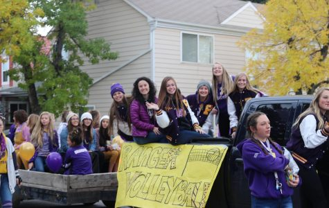 Volleyball players show off their purple and gold spirit in the homecoming parade