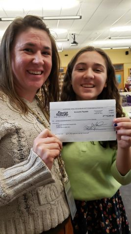 Green Initiative adviser Alecia Jongeward and team member Stella Davis hold the check for $15,000 from Sabanye Stillwater, which will help them install solar panels at Park High School, in the library on Nov. 18.