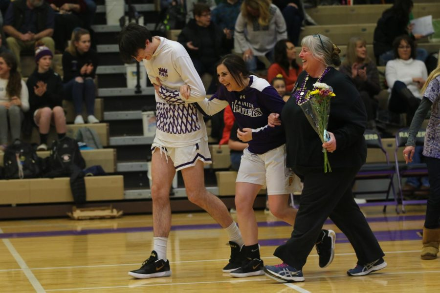 Brendon Johnson and Shania Johnson laugh with their mom as they walk onto the court during senior night introductions