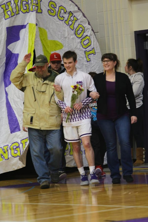 Eli Lanclos smiling with his support system as he is recognized during the 2020 senior night