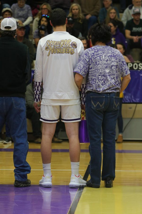 Sage McMinn and his parents listen in as his Coach speaks about the seniors on senior night