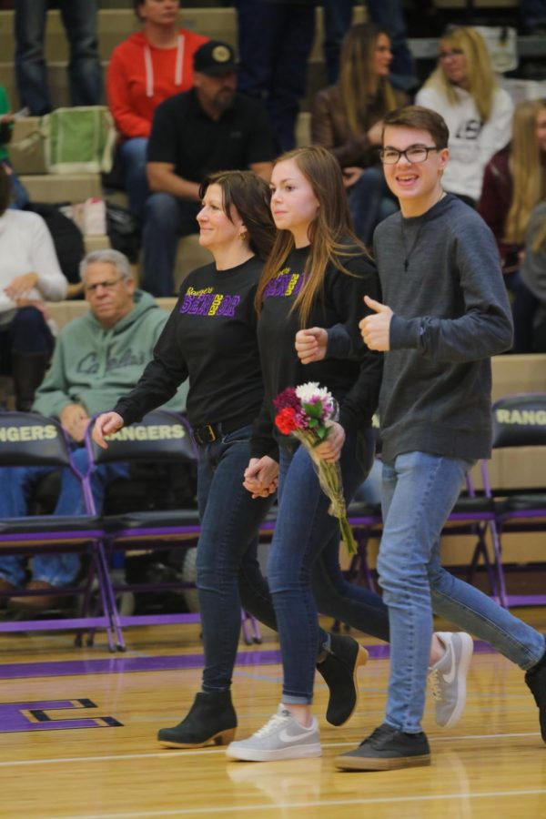 Brylea Beye walks with her mom and brother during senior night for cheerleaders