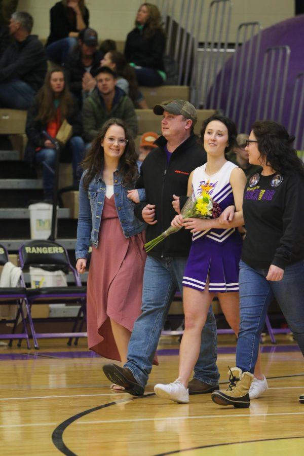 Senior cheerleader Riah Grandpre walking with her sister and parents for senior night