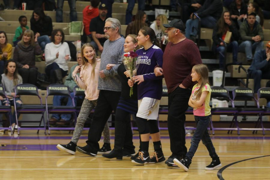 Bobbi Lima walking with her family in the gym during the basketball senior night presentation.
