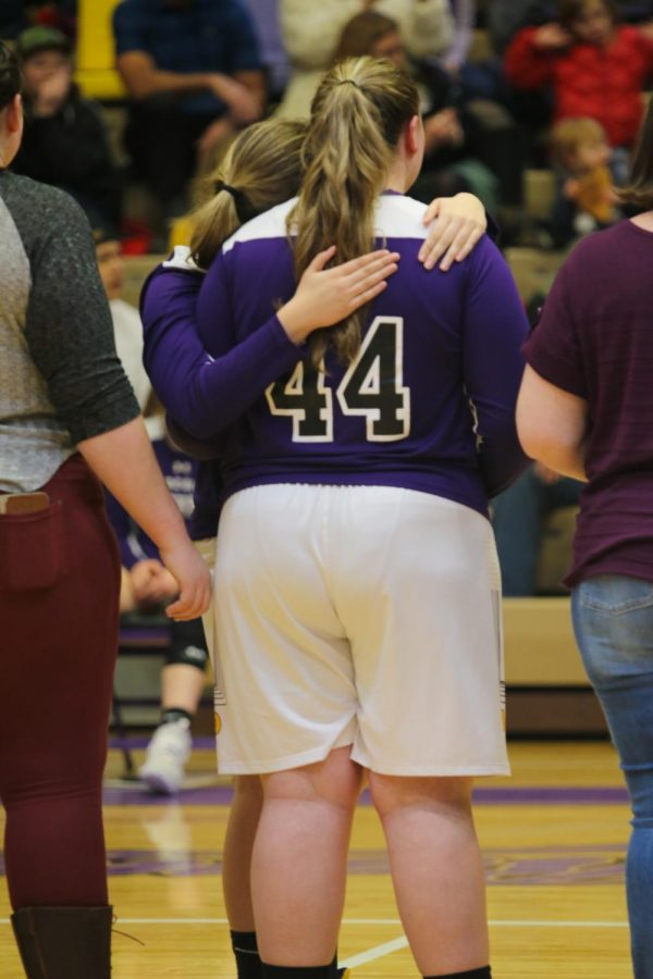 Senior Baylee Bergsing (44) accepts a hug from Alexis Orr, a junior basketball player, during the emotional 2020 senior night