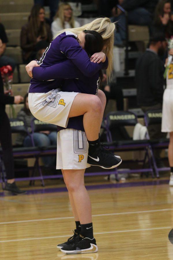 Shania Johnson embraces Skylar Higgs in a big hug after the girls basketball senior night