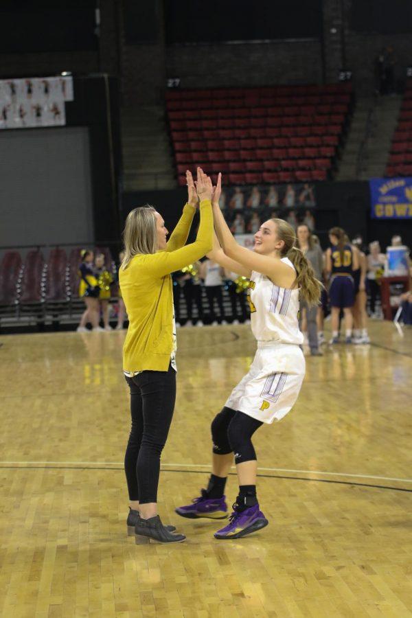 Coach Megan Burns high-fives Abby Kokot before the Miles City game.