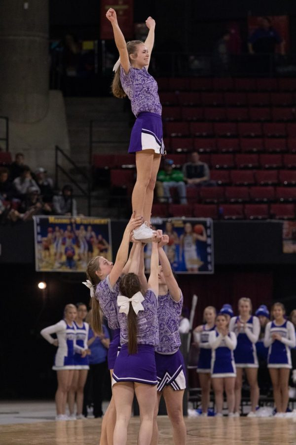 Kinley Hoeme stands proud as her team holds her up during a half time routine Wednesday afternoon.