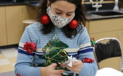 Athalia Windham sports a homemade Christmas present hat and self-decorated sweater while cutting out a virus snowflake in Mr. Mogen's class, Dec. 22.