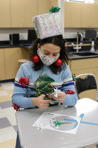 Athalia Windham sports a homemade Christmas present hat and self-decorated sweater while cutting out a virus snowflake in Mr. Mogen