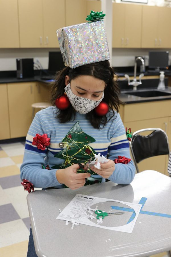 Athalia Windham sports a homemade Christmas present hat and self-decorated sweater while cutting out a virus snowflake in Mr. Mogens class, Dec. 22.