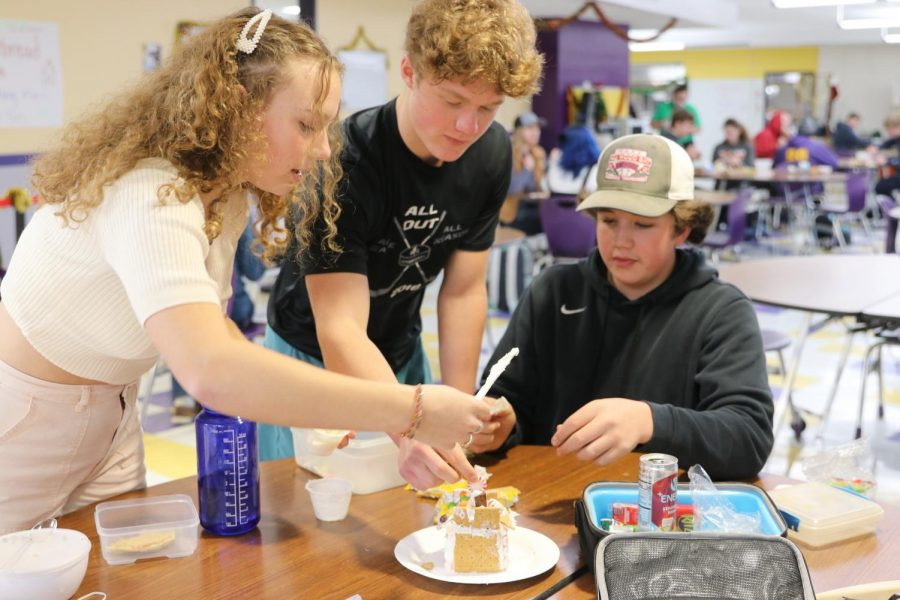 Cassiday Fletcher helps Cole Bartz and Jakob Cipriani put the finishing touches on their gingerbread house during first lunch, Dec. 21.