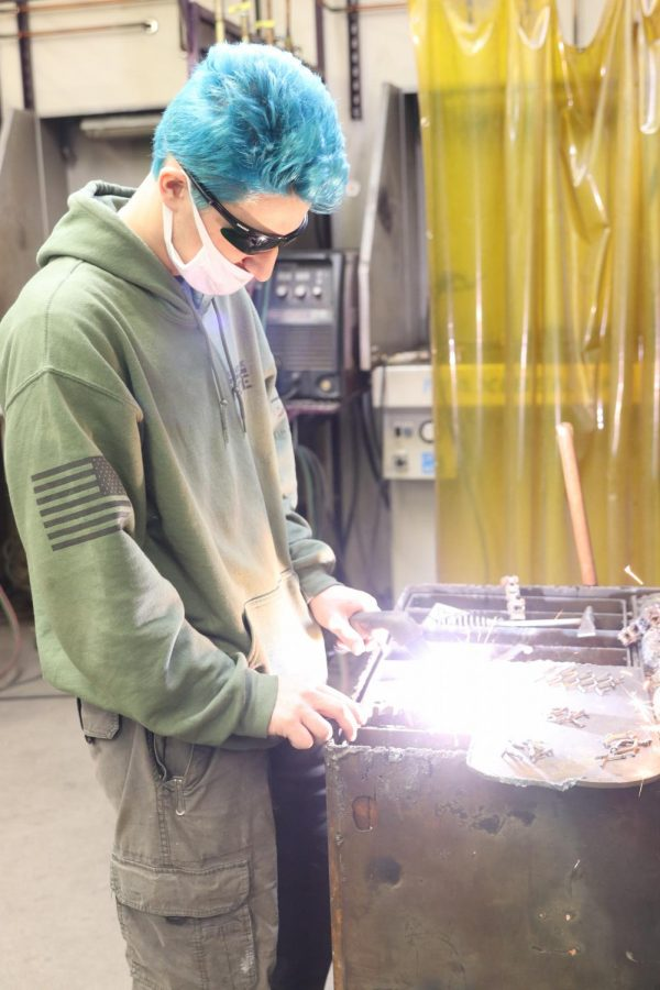 James Estes welds pieces of a holiday metals project on Dec. 21.