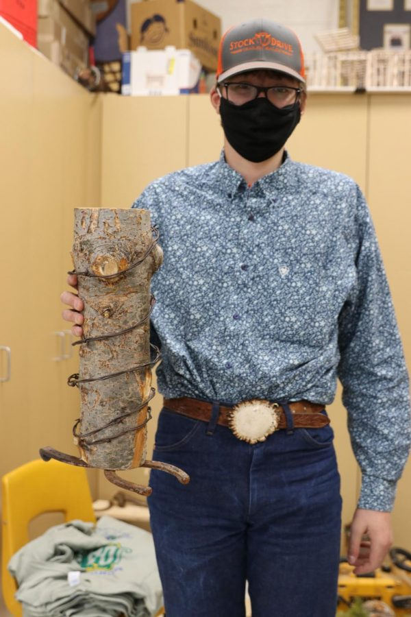 Layne Boeh holds up the log centerpiece that he created in Erica Timmermans Ag Ed 1 class.