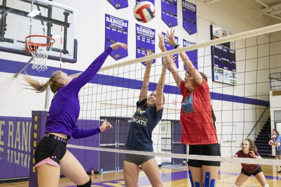 Emma Warhank and Hailey Strupp attempt to block a spike by Taylor Young during practice last week.